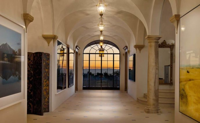 Feature corridor with groin vaulted ceilings showcasing art at sunset in an upscale estate.